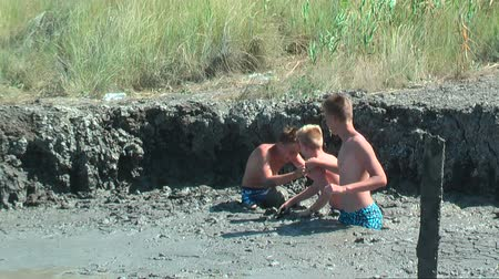boggy : Kuchugury, Russia - July 16, 2017: Azov scorching heat mud volcano. Boys take procedures with healing mud Stock Footage