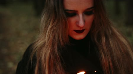 wicca : Witch with a book and candles in the forest