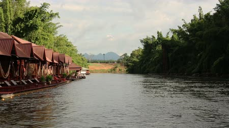 Footage of Kwai river shot while rafting. A tropical forest on the banks and and bungalows. The strong current of the water. Kanchanaburi,Thailand