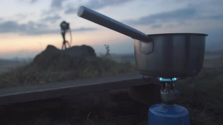 A pan with a handle stands and is heated on a gas burner against the sky