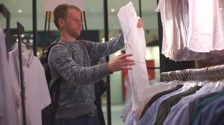 ubrania : guy 30 years old chooses clothes in the store Wideo
