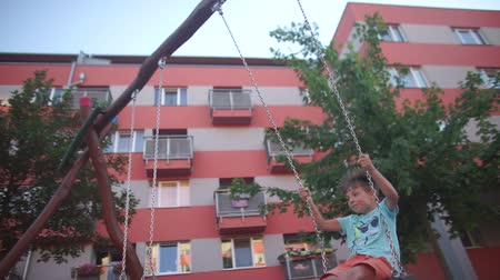 humanóide : a boy of 7 years riding on a swing against the background of a burgundy house in the city