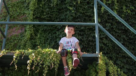 zarostlý : the child of 4 years in knee pads sits on a dangerous balcony covered with green plants