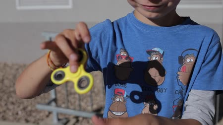 fidget spinner : a boy in a blue T-shirt and orange shorts is holding a spinner in his hand Stock Footage