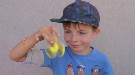 fad : a boy in a blue T-shirt and orange shorts is holding a spinner in his hand Stock Footage