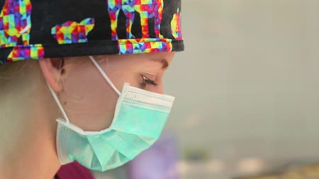 The eyes of a European young female surgeon. Concentrated look. A responsibility. Mask on the face. A funny colorful hat. Portrait. Blink. Close-up. Dostupné videozáznamy
