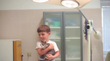 a child holds a cat in his hands in the operating room