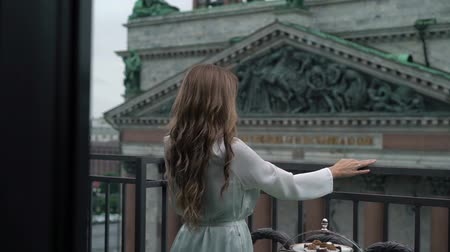 st isaac's cathedral : Woman on balcony in white dress at cloudy day Stock Footage