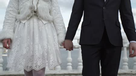 voronezh : Young lovely wedding couple walking on a street and taking hands at winter