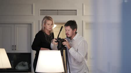 videocamera : Man and woman working with camera on tripod indoors Stock Footage