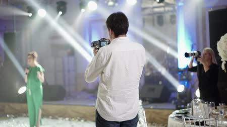 videocamera : Man and woman shooting photo and video on the party indoors Stock Footage