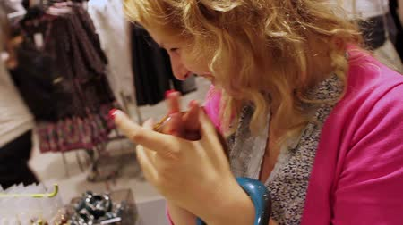 kajdanki : Young blonde woman in shop trying bracelet jewelry