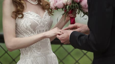 piwonie : Groom put on wedding ring on brides hand at wedding ceremony at cloudy day