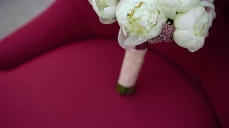piwonie : Wedding bouquet flowers on red chair Wideo