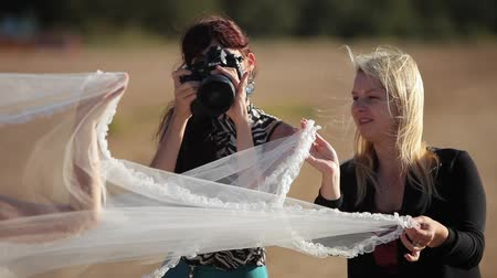 помощник : SAINT-PETERSBURG, RUSSIA - SEPTEMBER 19, 2014: Photographer taking photo of waving bridal veil at the beach