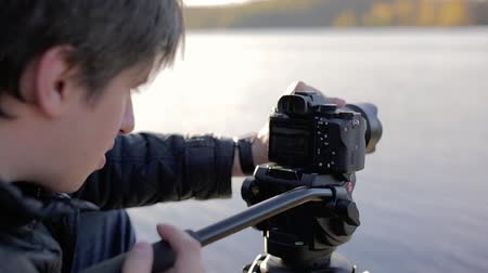 dop : Cameraman with camera on tripod at sunny autumn day outdoors Stock Footage