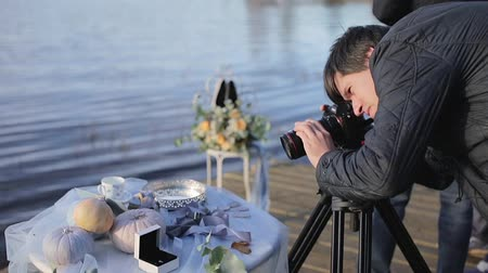 dop : Cameraman with camera on tripod at sunny autumn day outdoors shooting wedding decoration