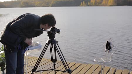 dop : Cameraman with camera on tripod at sunny autumn day outdoors shooting womans shoes