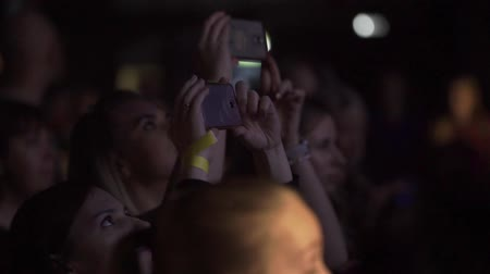 takes : SAINT-PETERSBURG, RUSSIA - MARCH 11, 2018: People takes photo and video on mobile phones at the concert in club slowmotion