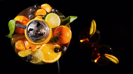 bulbo : Pair of glasses with alcoholic drink beverage wine cocktail and hookah with fruits black background isolated