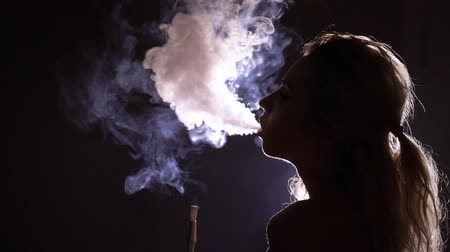 fuma : Young woman smoking hookah silhouette