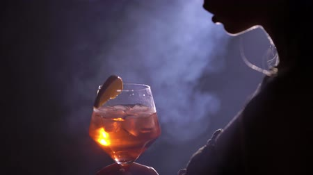 sparkling drink : Young woman with glass of cocktail silhouette black background with smoke