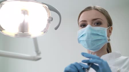 dişçi : Dentist doctor in dental clinic turn on light lamp and working with tools pov