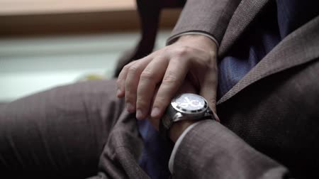 Man in brown suit looking at wrist watches indoors