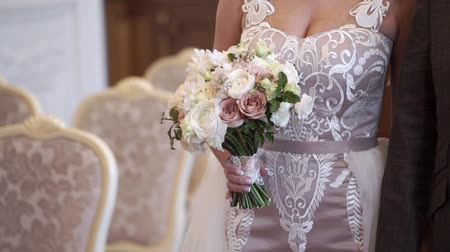 Bride holding bridal bouquet indoors at wedding ceremony Stock mozgókép