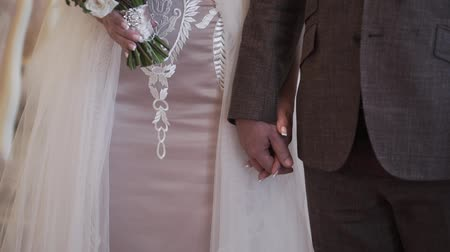 Bride and groom holding hands at wedding ceremony indoors
