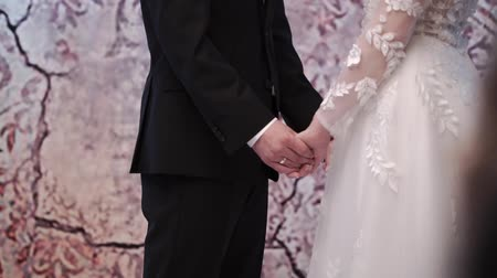 tomar : Bride and groom holding hands at wedding ceremony