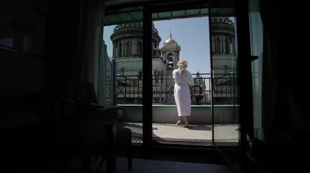 leaping : Young blonde woman at balcony in bathrobe
