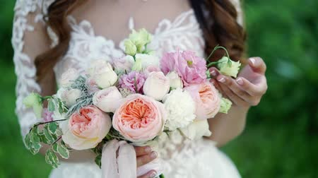 piwonie : Young bride touching bridal bouquet in a park
