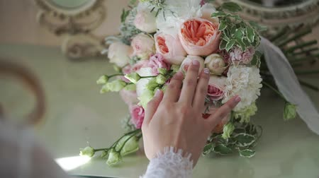 piwonie : Young bride touching bridal bouquet indoors Wideo