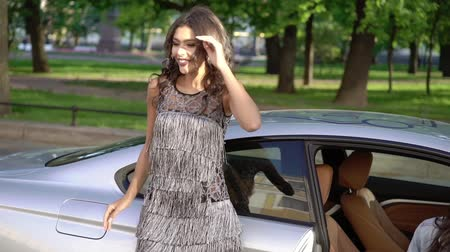 позы : Two young woman posing near luxury sports car in a city