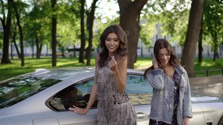 двухместная карета : Two young woman posing near luxury sports car in a city