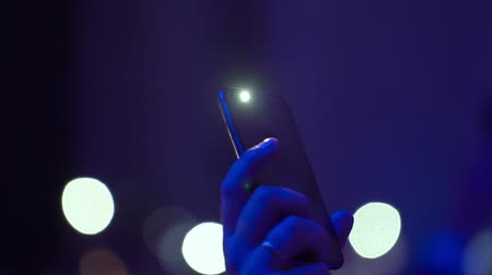 lanterna : People with flashlights waving hands at the party concert event light blurs