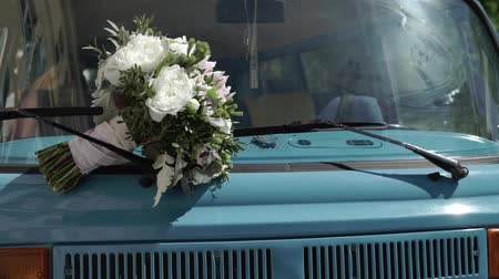volkswagen : Bridal bouquet on a hood of blue retro old bus Stock Footage