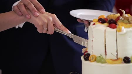nowożeńcy : Bride and grrom cutting pieces of white wedding celebration cake with fruits at the party event