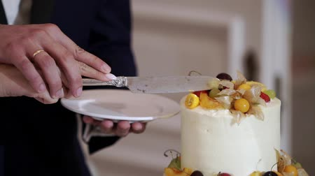 wedding cake : Bride and grrom cutting pieces of white wedding celebration cake with fruits at the party event