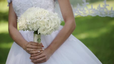 marad : Young beautiful bride in wedding white dress with bridal bouquet of white roses staying in a park at summer day slowmotion