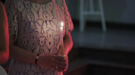 celebration event : Woman holding candle with fire in hand indoors at the evening in the dark Stock Footage