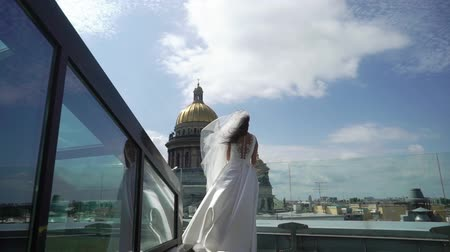st isaac's cathedral : Young bride staying on a terrace roof top with city view waving veil at sunny summer day slowmotion. View at Isaacs Cathedral in Saint Petersburg