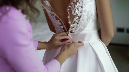 buttoning : Young woman wearing bridal dress at wedding day, bridemaid buttoning her dress
