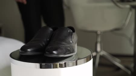 go away : Man takes black leather shoes in room and goes away