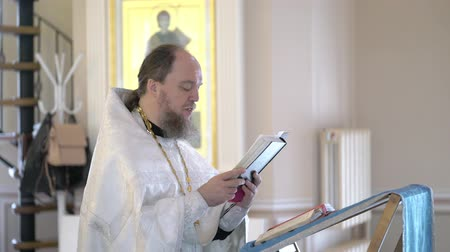 clergy : SAINT-PETERSBURG, RUSSIA - JULY 20, 2018: Priest praying with Bible book in church at ceremony