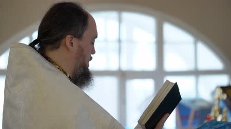 clergyman : SAINT-PETERSBURG, RUSSIA - JULY 20, 2018: Priest praying with Bible book in church at ceremony