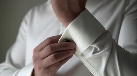 classical suit : Young man in white classical shirt put oncuff links