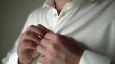 classical suit : Young man put on and buttoning white classical shirt