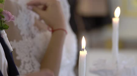 papież : Bride and groom holding candles in church at christianity ceremony